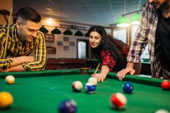 Billiard players with cues at the table with balls. Billiard players with cues at the table with colorful balls, poolroom. Group plays american pool game in royalty free stock images