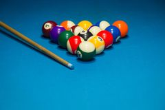 Billiard pool balls in triangle and stick on table. Billiards balls and cue on billiards table Royalty Free Stock Photos