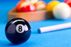 Billiard pool game eight ball with cue on billiard table. Billiard pool game eight ball with cue and eightball balls set up on billiard table with blue cloth Royalty Free Stock Photo