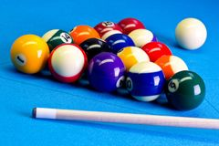 Billiard pool game eight ball setup with cue on billiard table. Billiard pool game eight ball with eightball balls set up with cue on billiard table with blue Royalty Free Stock Photos