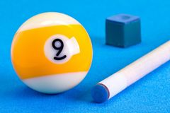 Billiard pool game nine ball with chalk and cue on billiard tabl. E with blue cloth Stock Photography