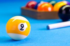 Billiard pool game nine ball with cue on billiard table. Billiard pool game nine ball with cue and nineball balls set up on billiard table with blue cloth Royalty Free Stock Photography