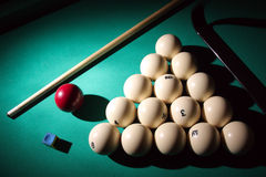 Billiard pyramid and cue on table. Stock Photography