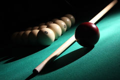 Billiard still life. Balls pyramid with number 8 ball on a foreground, cue and red ball on a light beam Royalty Free Stock Photos