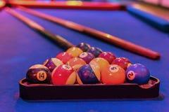 Billiard table balls and cue. Closeup photo of blue billiard table, balls and cue royalty free stock image