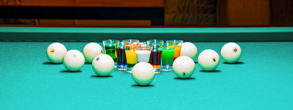 On a billiard table stand with coloured glasses of alcohol. Billiards, balls and stack Royalty Free Stock Images