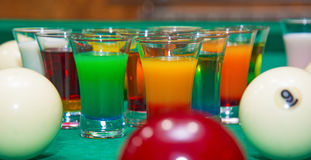 On a billiard table stand with coloured glasses of alcohol. Billiards, balls and stack Royalty Free Stock Image