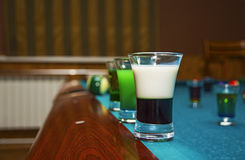 On a billiard table stand with coloured glasses of alcohol. Billiards, balls and stack Stock Image