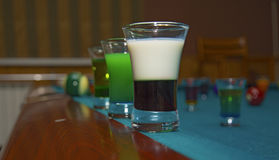 On a billiard table stand with coloured glasses of alcohol. Billiards, balls and stack Royalty Free Stock Photo