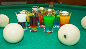 On a billiard table stand with coloured glasses of alcohol. Billiards, balls and stack Stock Photo