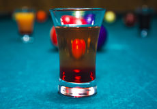 On a billiard table stand with coloured glasses of alcohol. Billiards, balls and stack Royalty Free Stock Photography