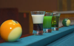 On a billiard table stand with coloured glasses of alcohol. Billiards, balls and stack Stock Photography