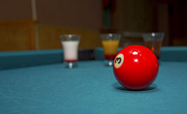 On a billiard table stand with coloured glasses of alcohol. Billiards, balls and stack Stock Photos