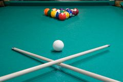 On the billiard table are two cues crossed against the background of gaming balls stock images