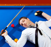 Billiard young man player lying on pool blue table Stock Photos