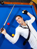 Billiard young man player lying on pool blue table Stock Image
