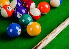 Billiardbollar på den gröna tabellen med billiardstickrepliken, snooker, Fotografering för Bildbyråer