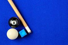 Billiardbollar, stickreplik och krita i en blå pöltabell Royaltyfri Foto