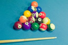 Billiards balls and cue on billiards table royalty free stock photography