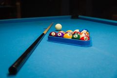 Billiard pool balls in triangle and stick on table. Billiards balls and cue on billiards table Royalty Free Stock Photography