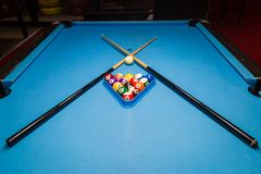 Billiard pool balls in triangle and sticks on table. Billiards balls and cue on billiards table Stock Photos
