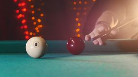 Billiards club. A person playing billiards. A cue hitting the ball with number eight