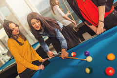 Billiards game. Group of friends playing pool together. Royalty Free Stock Photos