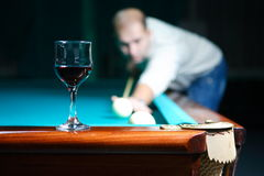 Billiards and men. The young man stands up for a billiard table with a cue in hands against a dark background Stock Images