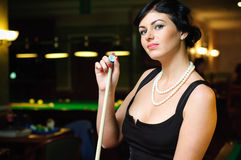 Billiards player. Pretty girl holds a cue and looks skittish at camera Royalty Free Stock Photos