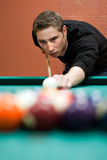Billiards Player. A young man lines up his shot as he breaks the balls for the start of a game of billiards. Shallow depth of field royalty free stock photography