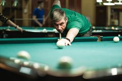 A pool player takes aim at the ball. Billiards player plays Billiards aiming at the ball stock photos