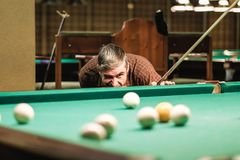 A pool player takes aim at the ball. Billiards player plays Billiards aiming at the ball royalty free stock photography