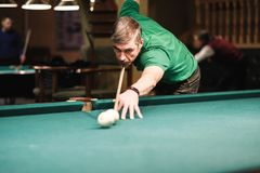 A pool player takes aim at the ball. Billiards player plays Billiards aiming at the ball royalty free stock image