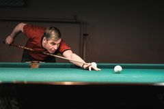 A pool player takes aim at the ball. Billiards player plays Billiards aiming at the ball royalty free stock photo