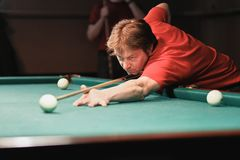 A pool player takes aim at the ball. Billiards player plays Billiards aiming at the ball stock image