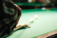 A pool player takes aim at the ball Royalty Free Stock Photography
