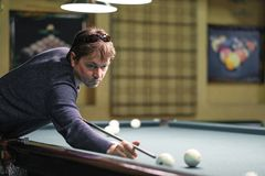 A pool player takes aim at the ball. Billiards player plays Billiards aiming at the ball stock photo