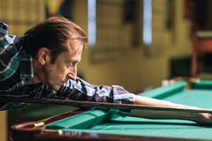 A pool player takes aim at the ball. Billiards player plays Billiards aiming at the ball stock photography