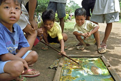 Billiards playing Filipino children. Philippines, island Mindanao; boys billiards on the ground in the street with marbles and pool cue. The youngsters have a royalty free stock photography