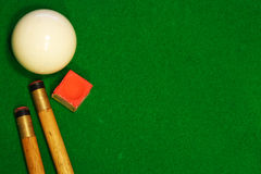 Billiards table cues and cue ball. A green cloth billiards or pool table background with cues, cueball and chalk stock photo