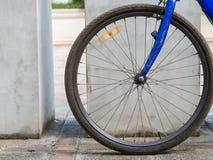 Billiges blaues altes Fahrrad parkt nahe den Bäumen, Vorderrad Stockfoto