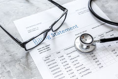 Billing statement for for medical service in doctor`s office background. Billing statement for for medical service in doctor`s office on stone desk background Royalty Free Stock Photography