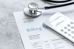 Billing statement for for medical service in doctor`s office background. Billing statement for for medical service in doctor`s office on stone desk background Stock Image