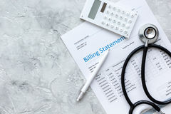 Billing statement for for medical service in doctor`s office background top view mock up. Billing statement for for medical service in doctor`s office on stone Stock Photo