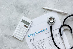 Billing statement for for medical service in doctor`s office background top view. Billing statement for for medical service in doctor`s office on stone desk Royalty Free Stock Images