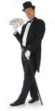 Billionaire. Man in tuxedo, top hat and cane fanning himself with stacks of money royalty free stock photos