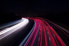 Billjus på huvudvägen med en mörk natt royaltyfri fotografi