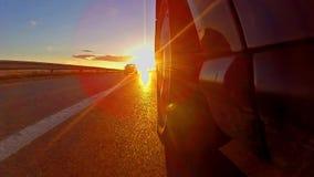 Billoppet med solnedgång rays att skina på gummihjulet