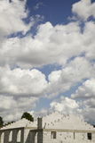 A billow of clouds. This picture shows a big billow of white clouds above a white unfinished brick building. It was taken on a sunny summer day in Poland. The Stock Photo