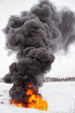 Billowing black smoke. Over a orange fire Stock Photo